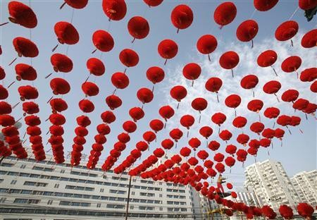 A worker prepares red lantern decorations for the Spring Festival Temple Fair at the entrance to Ditan Park in Beijing, Jan. 20, 2009.