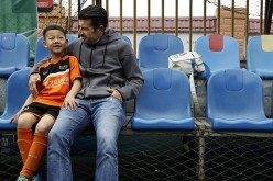 Luis Figo talks to a young Chinese boy who attended a football clinic conducted by the Figo Football Academy.
