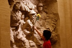 A boy places a flower on a sculpture depicting Chinese fighters during the World War II.