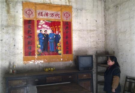 A Chinese villager looks up at a political poster.