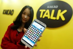 A Kakao Talk employee displays a mobile game on a smartphone at the company's headquarters in Seongam, South Korea.