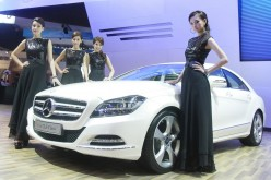 Models pose beside a new Mercedes-Benz CLS during the 32nd Bangkok International Motor Show in Bangkok, March 24, 2011.