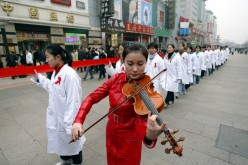 Peking University students parade through a major shopping street in Beijing to promote awareness of AIDS, Nov. 30, 2003.