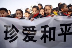 Children hold a banner saying