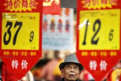 A customer looks at price tags at a supermarket in Huaibei, Anhui Province, Feb. 10, 2015.