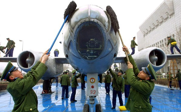PLAAF soldiers clean up a bomber plane on display at a military museum.