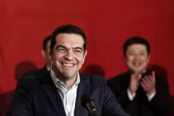 Greek Prime Minister Alexis Tsipras smiles during his speech aboard the Chinese frigate Changbaishan.