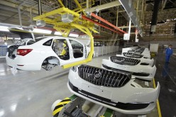 An employee looks on next to an assembly production line of Buick cars at a General Motors factory in Wuhan, Hubei Province, Jan. 28, 2015.