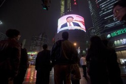 People in China watch a huge public TV screen showing a news broadcast.