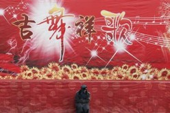 A guard sits in front of a Chinese New Year celebration stage in China.