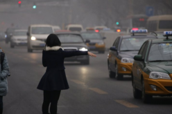 A woman trying to hail a taxi in China.