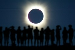 Tourists watch the sun being blocked by the moon during a solar eclipse in the Australian outback town of Lyndhurst, located around 700 kilometres (437 miles) north of Adelaide December 4, 2002. The town is one of only four in Australia where the 26 secon