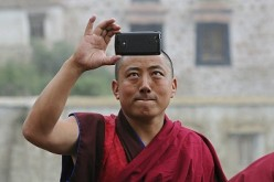A Tibetan monk takes a picture of himself, a