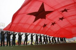 People's Liberation Army (PLA) soldiers wave a Chinese national flag for National Day in Beijing.