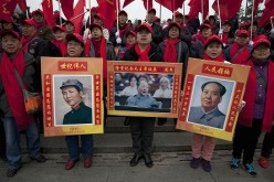 People hold posters of former Communist Party leader Mao Zedong during his 121st birth anniversary.