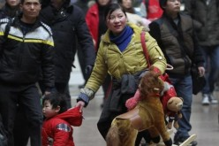 A woman holds her child with one hand and toys with the other at a railway station in Beijing, Jan. 14, 2014.