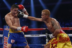 Amnat Ruenroeng (R) of Thailand punches double Olympic flyweight champion Zou Shiming of China during their IBF world flyweight title fight in Macau, March 7, 2015
