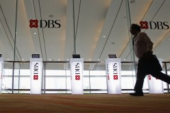 A man runs past Development Bank of Singapore (DBS) logos at a DBS function in Singapore, July 5, 2013.