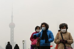 Women wear face masks in front of the Oriental Pearl TV Tower during a hazy day in downtown Shanghai, Jan. 26, 2015.