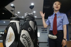 An officer talks beside confiscated counterfeit golf clubs during a presentation in Beijing. Chinese regulators have been putting increasing pressure on businesses over fake goods.