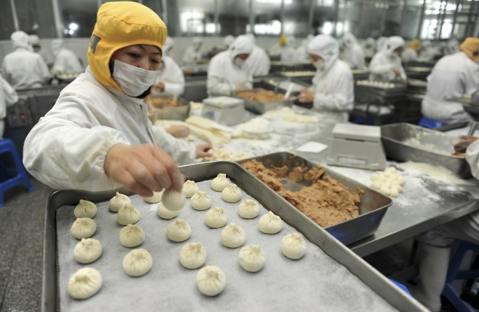 An employee makes stuffed steamed buns at a food factory in Yangzhou, Jiangsu Province.