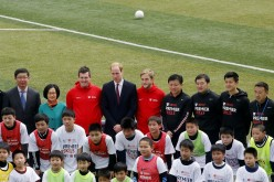 Britain's Prince William (rear C) poses for a group picture during a visit to a Premier League training camp at Nanyang Secondary School in Shanghai, March 3, 2015.
