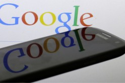A Google logo is reflected on the screen of a Samsung Galaxy S4 smartphone in this photo illustration taken in Prague January 31, 2014. Google Inc and Samsung Electronics Co Ltd, which are frequently involved in patent infringement lawsuits but not agains