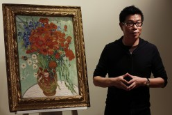 Wang Zhongjun, chairman of Huaiyi Brothers Media, stands beside Vincent van Gogh's