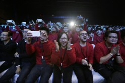 Xiaomi staff and users of Xiaomi phones react at the launch ceremony of the Mi Note in Beijing, Jan. 15, 2015.