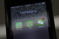 Icons of messaging applications WhatsApp of Facebook (L), Laiwang of Alibaba Group (C), and WeChat (Weixin) of Tencent Group are seen on the screen of a smartphone.