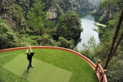 A golf player hits a shot toward a putting green on a lake from a tee ground on top of a hill, at Zhangjiajie, Hunan Province, Sept. 23, 2014.