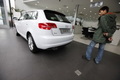 A man looks at a new Audi A3 car at a Volkswagen auto dealership in Shanghai, March 20, 2013.
