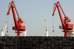 Piles of steel pipes to be exported are seen in front of cranes at a port in Lianyungang, Jiangsu Province, March 7, 2015.