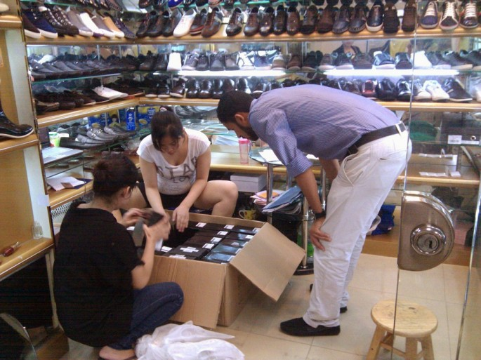 A customer looks at fake foreign brand shoes inside a store at Baiyun World Leather Market in the southern Chinese city of Guangzhou.