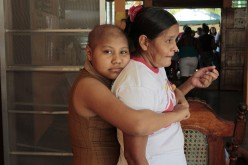 A girl, who is a cancer patient, embraces her mother after a march to observe the international day of the fight against childhood cancer in Managua, Feb. 14, 2015.