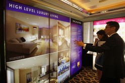 A sales representative speaks to a visitor in front of photographs of a London upmarket property development for sale, inside a luxury hotel in Hong Kong.