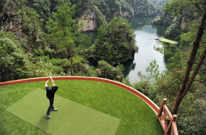A staff member plays a shot toward a putting green on a lake from a tee ground on top of a hill, at Zhangjiajie, Hunan Province.