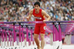 China's Liu Xiang looks up after kissing the last hurdle in his lane during his men's 110-meter hurdles round 1 heat at the London 2012 Olympic Games.