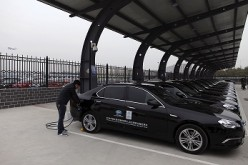A man charges the batteries of BAIC Motors electric cars at a charging station at the Beijing Capital International Airport in Beijing.