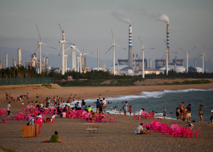 Windmills and a power plant can be seen in the distance as beachgoers watch sunset in the city of Dongfang on the western side of China's island province of Hainan.