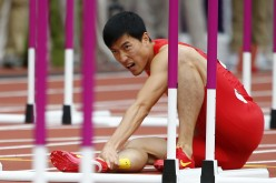 China's Liu Xiang holds his leg after suffering an injury in his men's 110m hurdles round 1 heat at the London 2012 Olympic Games at the Olympic Stadium, Aug. 7, 2012.