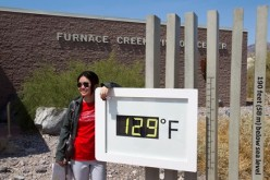 A student from China poses in front of an unofficial temperature gauge at the Furnace Creek Visitor Center in Death Valley National Park in California.