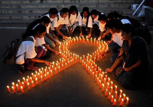 Staff members of a government-run pharmaceutical college light candles