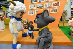 A boy interacts with two cartoon figures during 2015 China International Cartoon and Animation Festival in Hangzhou, Zhejiang Province, on Tuesday, April 28, 2015.