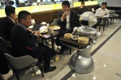 A robot delivers food orders of customers at a restaurant in Hefei, Anhui Province.