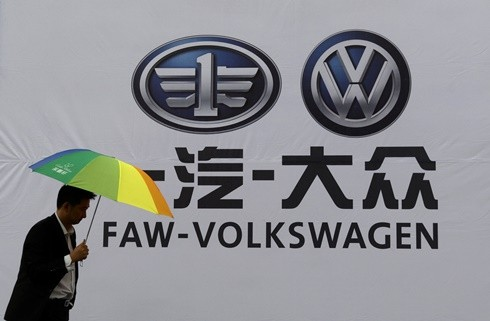 A man walks past a company logo of FAW-Volkswagen at an automobile exhibition in Fuyang, Anhui Province.