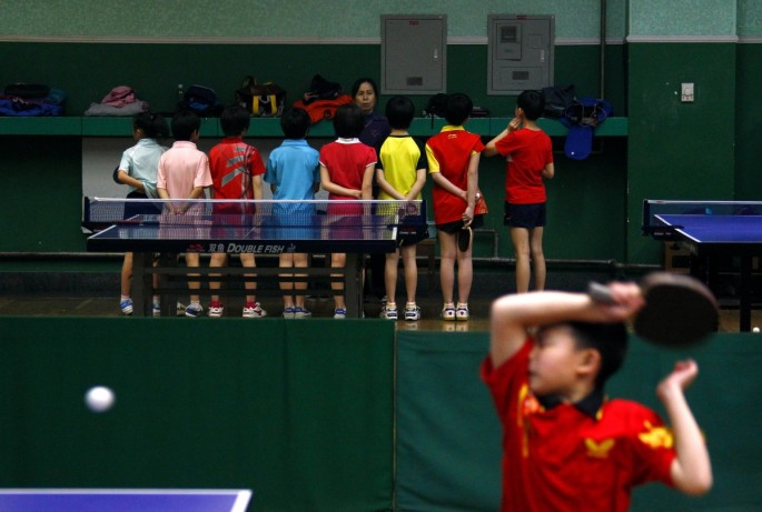 A coach talks to students as another hits a shot during a table tennis class at the Shichahai Sports School in Beijing.