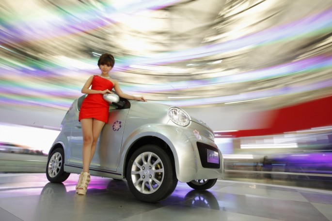 A model poses next to a Dongfeng EJ02 during the opening day of the Shanghai Auto Show.