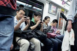 Passengers in a train try to access the Web using their mobile phones.