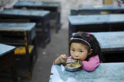 A lone child eats inside a classroom.